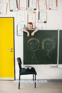 Boy hanging on blackboard stock photo