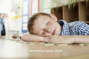 Boy sleeping on desk in classroom Stock Photo