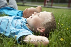 Boys resting laying in grass Stock Photo