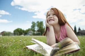 Red hair Girl reading book outdoors in grass stock photo