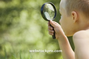 Little boy with a magnifying glass stock photo
