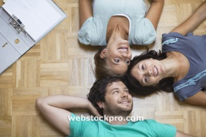 Young people lying on floor head to head stock photo