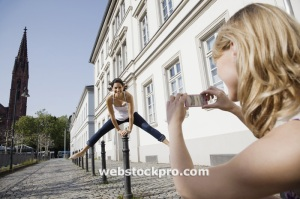 Young woman photographing friend jumping stock photo