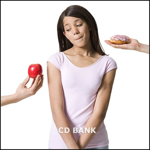 Close-up of a girl looking at an apple and donut