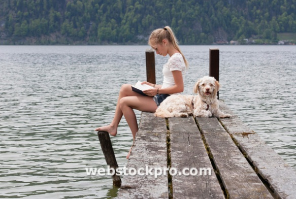 Austria, Teenage girl reading book beside dog on jetty
