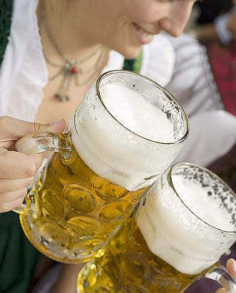 Women clinking litres of beer together (Oktoberfest, Munich) Stock Photo