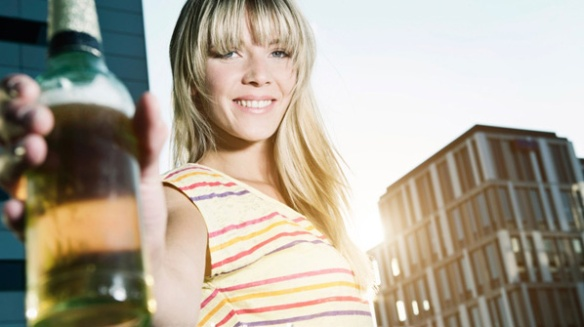 Young woman holding beer bottle, smiling, portrait Stock Photo